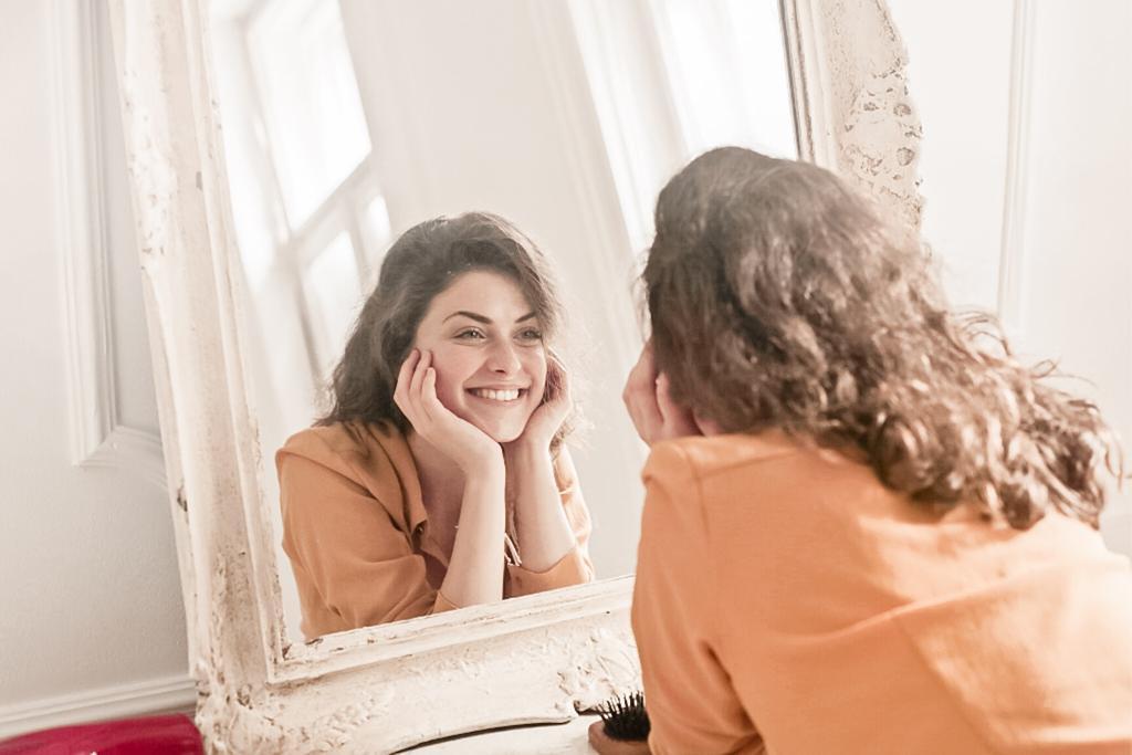 El peor espejo que puede existir, falta de identidad, chica sonriendo mientras se mira al espejo,